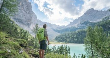 Young man contemplating nature by the mountain lake in Alto Adige in South Tyrol region, Italy
